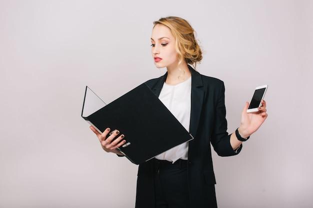 Femme D'affaires Jolie Blonde Confiante En Costume De Bureau Regardant Le Dossier Dans Les Mains, Tenant Le Téléphone. être Occupé, Travailleur, Secrétaire, Exécutif, Réussir Photo gratuit