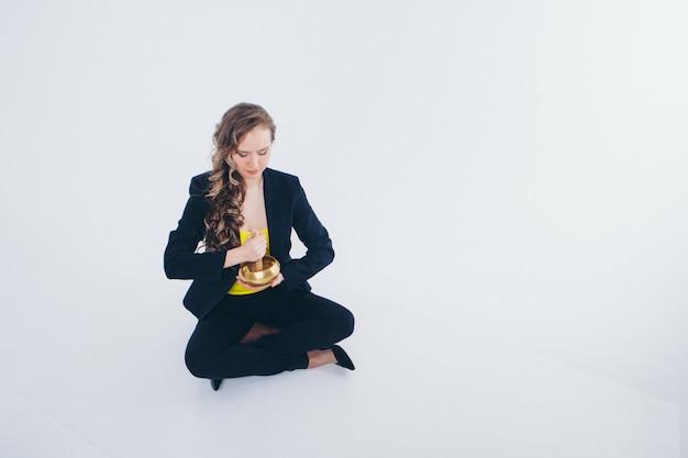 Femme Affaires, Méditer Préparation D'une Potion Sur Un Blanc. Bol Chantant Avec Mantra Bouddhiste Dans La Main D'une Femme En Costume Photo Premium