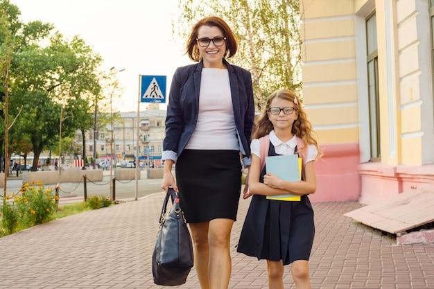 Femme d'affaires mère emmène l'enfant à l'école Photo Premium