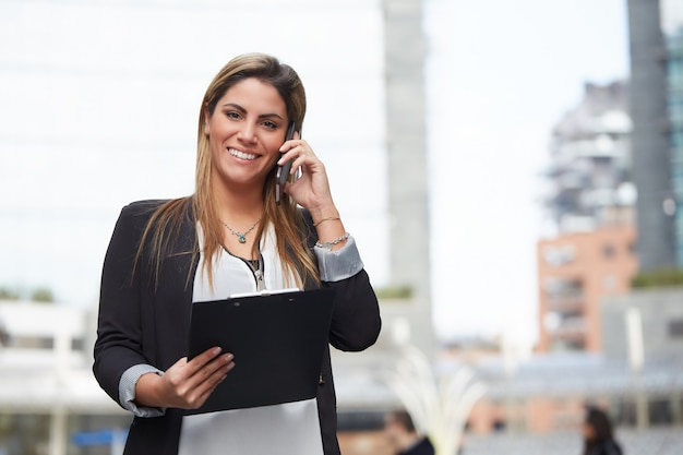 Femme d'affaires en milieu urbain parlant au mobile Photo Premium