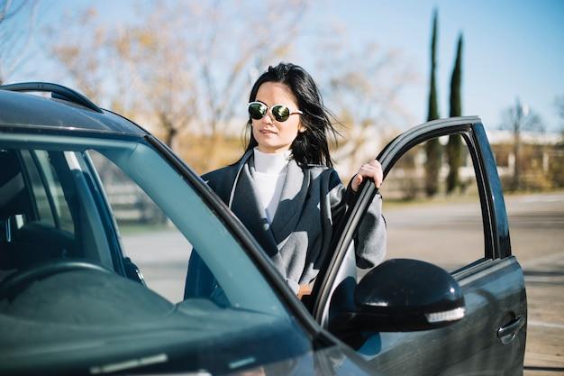 Femme d'affaires moderne, debout à côté de la voiture Photo gratuit