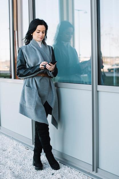 Femme d'affaires moderne utilisant un smartphone à l'extérieur Photo gratuit