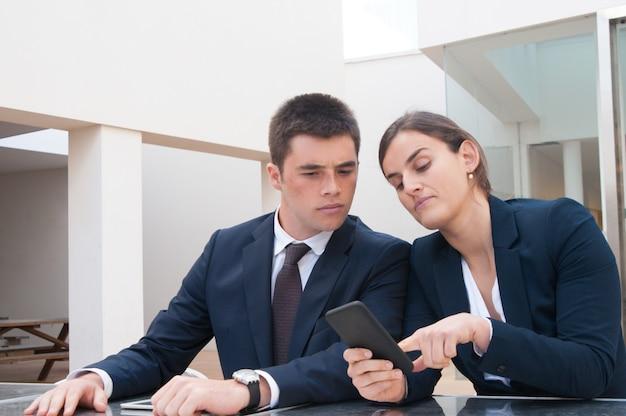 Femme d'affaires montrant des informations sur l'écran du téléphone à un collègue Photo gratuit