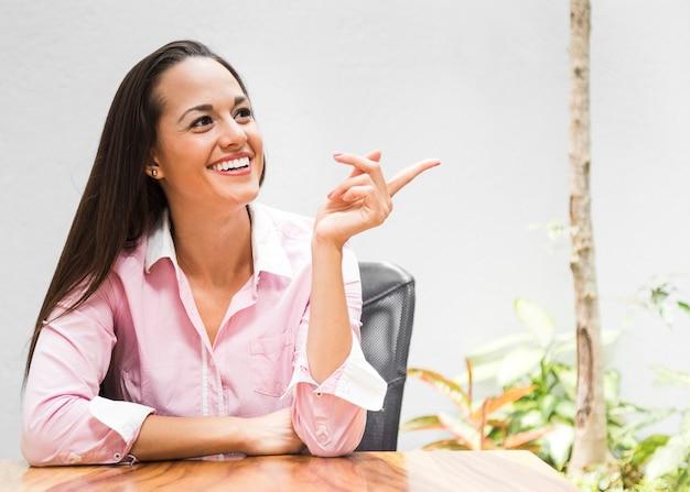 Femme d'affaires moyen coup pointant dans une direction Photo gratuit