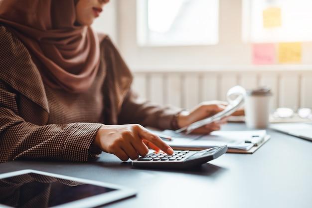Femme d'affaires musulmane travaillant sur les finances avec le rapport de l'entreprise et la calculatrice à la maison. Photo Premium