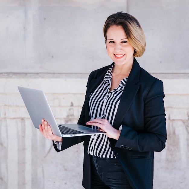 Femme d'affaires, navigation sur ordinateur portable dans la rue Photo gratuit