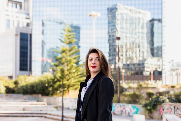 Femme d'affaires en noir debout dans la rue Photo gratuit