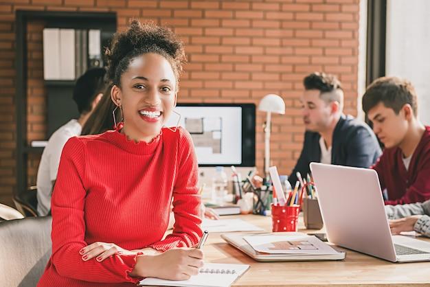 Femme d'affaires noir en haut rouge décontracté à la réunion de bureau Photo Premium