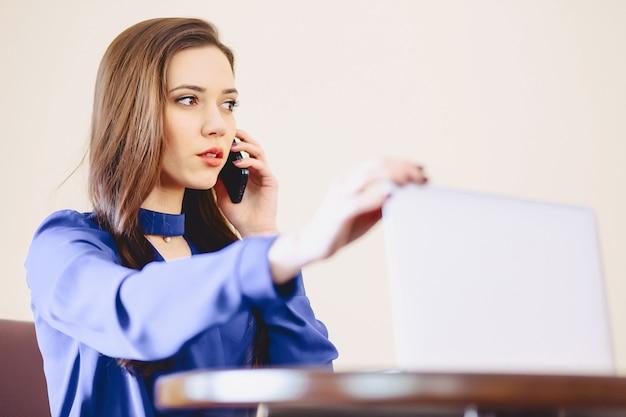 Femme d'affaires parle par téléphone au bureau et travaille sur un ordinateur portable Photo Premium