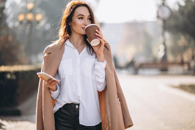 Femme d'affaires parler au téléphone et boire du café Photo gratuit