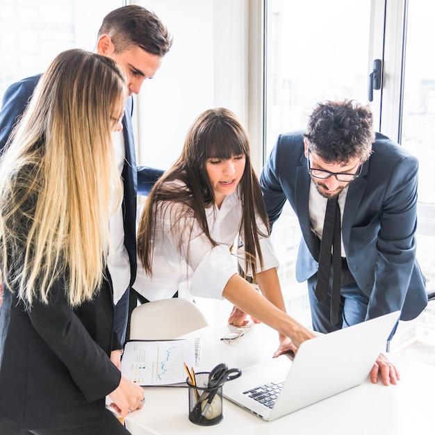 Femme d'affaires partageant ses idées créatives avec son collègue à l'aide d'un ordinateur portable Photo gratuit