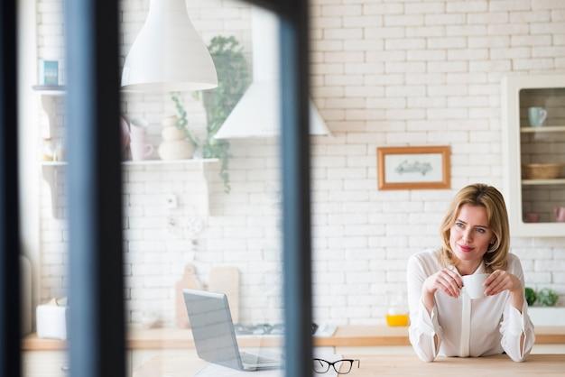 Femme D'affaires Pensif Assis Avec Une Tasse à Café Et Un Ordinateur Portable Photo gratuit