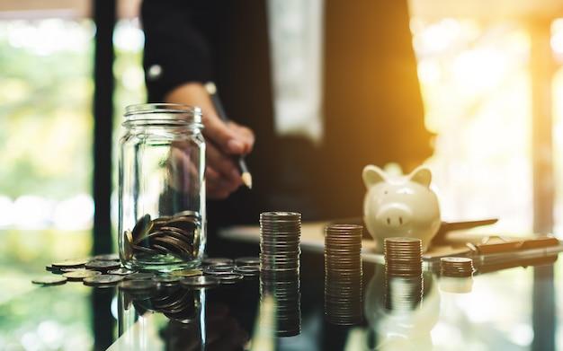 Femme Affaires, Pièces, Pile, Verre, Argent, Pot, Tirelire, Table, économie, Financier, Concept Photo Premium