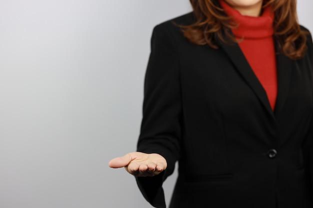 Femme D'affaires Portant L'uniforme De Costume Noir Et Rouge Avec Confiance Tout En Montrant Quelque Chose Sur Sa Main Photo Premium
