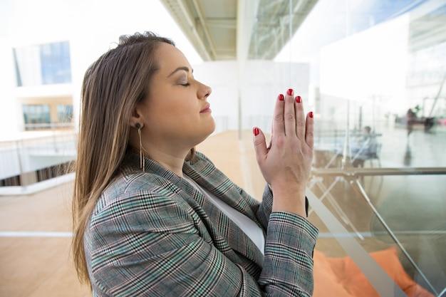 Femme d'affaires priant et gardant les mains ensemble à l'extérieur Photo gratuit