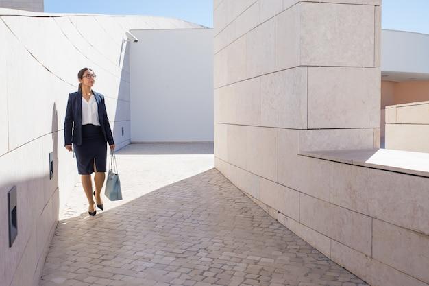 Femme d'affaires prospère se promener dans le centre d'affaires moderne Photo gratuit