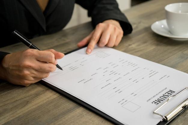 Femme d'affaires qui postule pour un emploi écrit sur cv en entreprise Photo Premium
