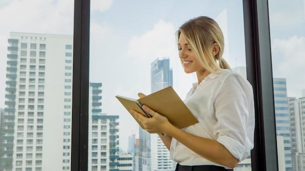 Femme d'affaires réfléchie au bureau écrit dans un cahier Photo Premium