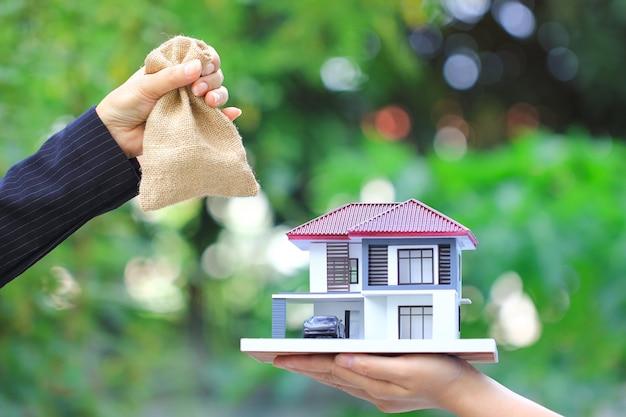 Femme D'affaires A Remis L'argent Dans Un Sac à Une Femme Tenant Une Maison Modèle Et Une Voiture, Nouvelle Maison Et Concepts De Trading Immobilier Photo Premium
