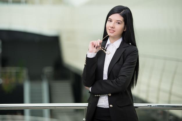 Femme d'affaires réussie à la recherche de confiance et souriante Photo Premium