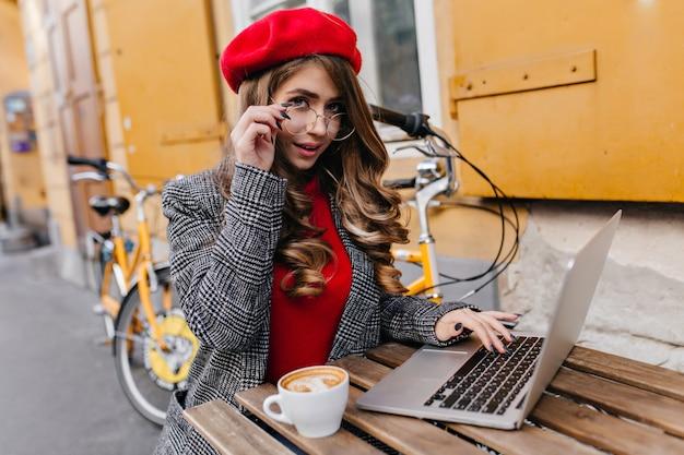 Femme D'affaires Romantique Travaillant Avec Un Ordinateur Portable Tout En Buvant Du Café Dans Une Froide Journée D'automne Photo gratuit