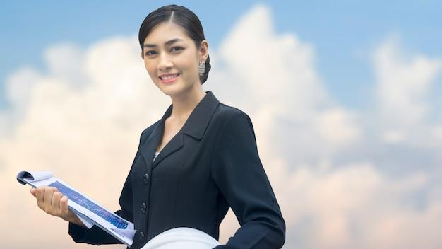 Femme d'affaires se dresse avec confiant et casque de construction Photo Premium