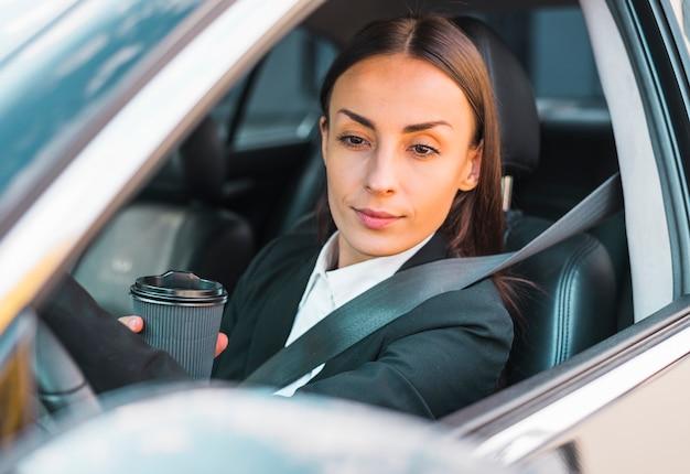 Femme affaires, séance, intérieur, siège auto, tenue, jetable, tasse café Photo gratuit