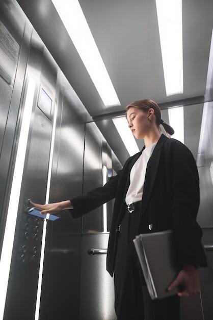 Femme D'affaires Sérieuse En Appuyant Sur Le Bouton De L'ascenseur Tenant Le Smartphone Dans Une Main Photo Premium