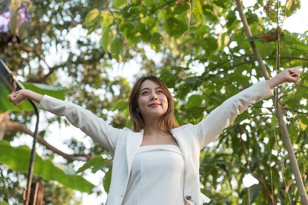Femme d'affaires a soulevé les bras avec bonheur et rafraîchissante dans la belle journée. Photo Premium