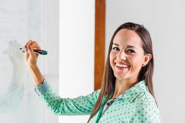 Femme d'affaires souriant et écrivant sur un tableau blanc Photo gratuit