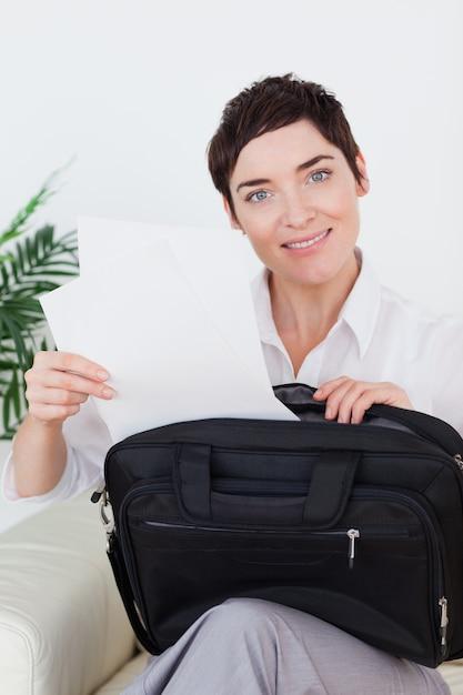 Femme D'affaires Souriant, Mettre Des Papiers Dans Son Sac Photo Premium