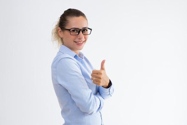 Femme d'affaires souriant montrant le pouce en haut et en regardant la caméra Photo gratuit