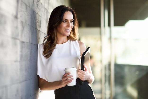 Femme D'affaires Souriant Prenant Une Pause-café Dans Un Immeuble De Bureaux. Photo Premium