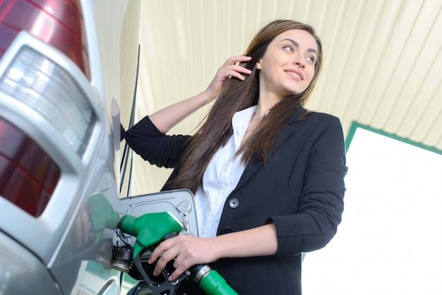 Femme d'affaires sur une station-service, tout en remplissant votre voiture. Photo Premium