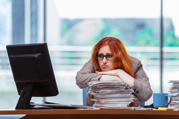 Femme d'affaires stressée avec une pile de papiers Photo Premium