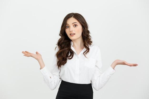 Femme d'affaires surprise montrant le produit. belle fille tenant la main sur le côté Photo Premium