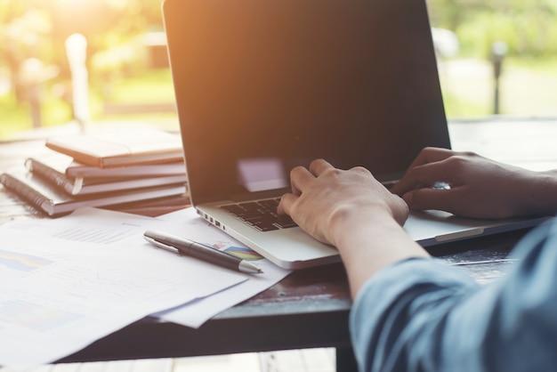 Femme d'affaires en tapant des mains sur un ordinateur portable clavier avec cha financier Photo gratuit