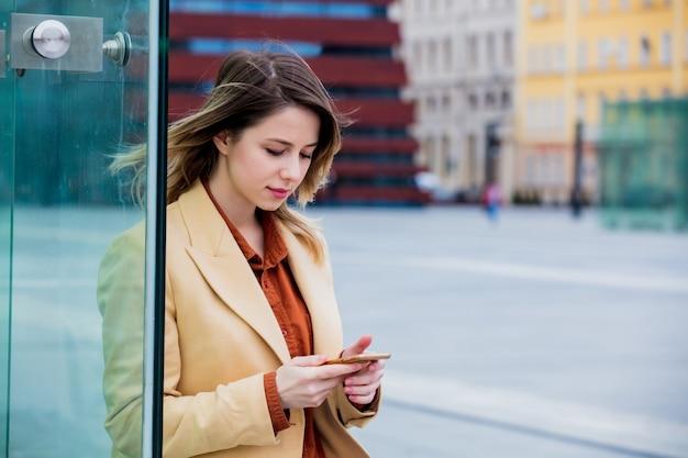 Femme d'affaires taper un message par téléphone sur la place de la ville Photo Premium