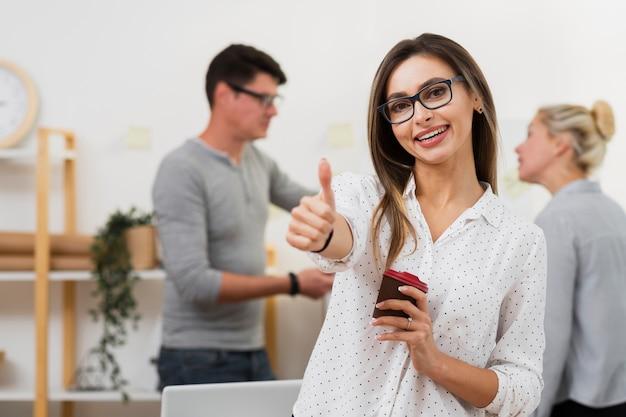 Femme d'affaires tenant une tasse de café et montrant un signe ok Photo gratuit