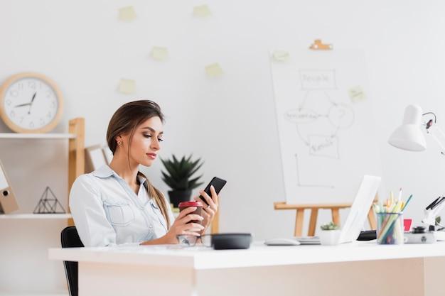Femme d'affaires tenant une tasse de café et regardant au téléphone Photo gratuit