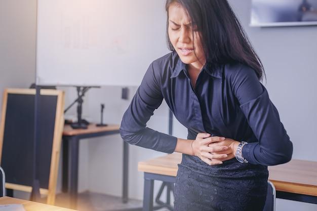 Femme d'affaires touchant l'estomac souffrant de maux d'estomac douloureux en raison de la menstruation. Photo Premium