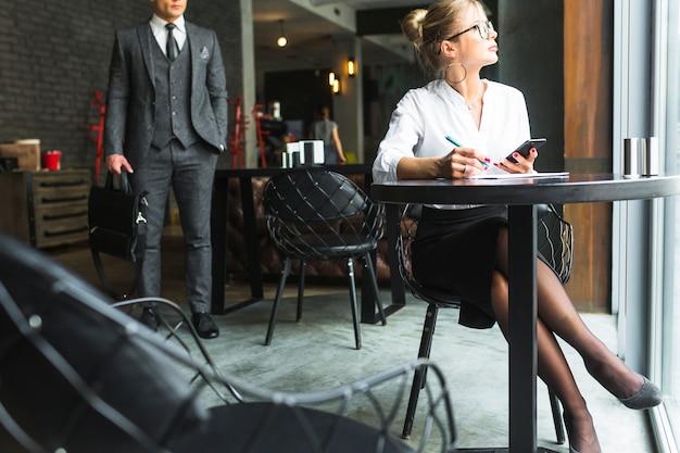Femme d'affaires travaillant sur un document dans un restaurant Photo gratuit