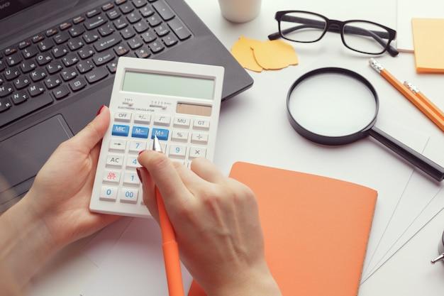 Femme d'affaires travaillant avec des données financières à la main à l'aide de la calculatrice Photo Premium