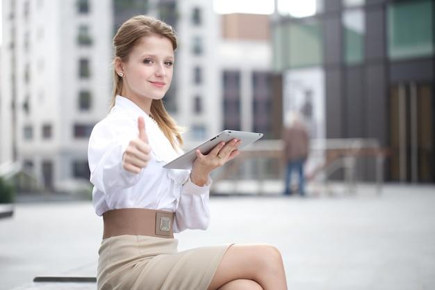 Femme d'affaires travaillant à l'extérieur de l'immeuble de bureaux avec des appareils numériques Photo Premium