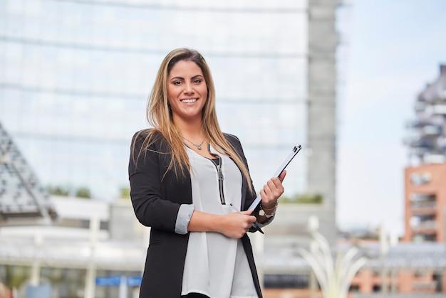 Femme d'affaires travaillant à l'extérieur de l'immeuble de bureaux Photo Premium