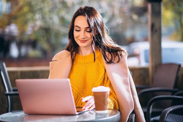 Femme d'affaires travaillant sur un ordinateur et buvant du café Photo gratuit