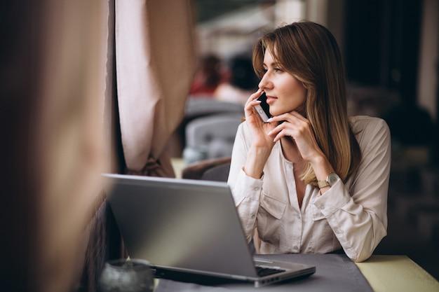 Femme d'affaires travaillant sur un ordinateur portable dans un café Photo gratuit