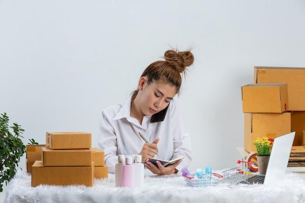 Une Femme D'affaires Travaille En Ligne Et Cherche à Répondre Au Client à L'emballage Du Bureau à Domicile Sur Le Mur. Photo gratuit