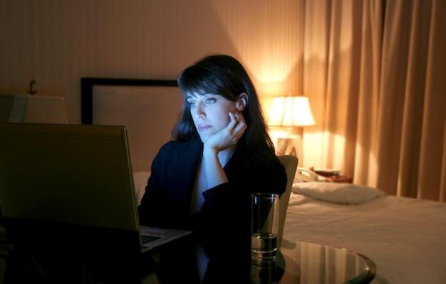 Femme D'affaires Utilisant Un Ordinateur Portable Dans Une Chambre D'hôtel Photo Premium