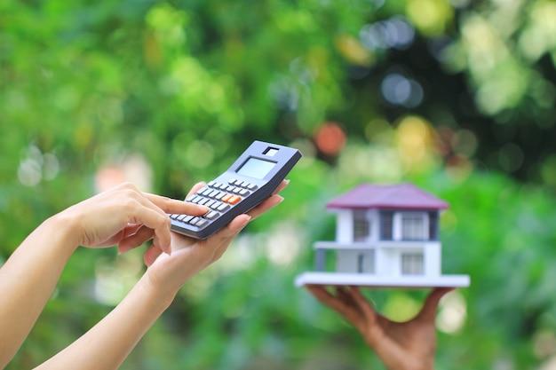 Femme affaires, utilisation, calculatrice, et, maison bois, sur, vert Photo Premium